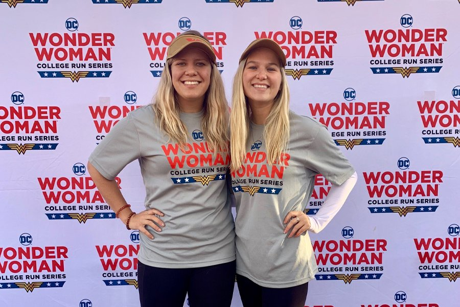 two women posing in front of wonder woman banner